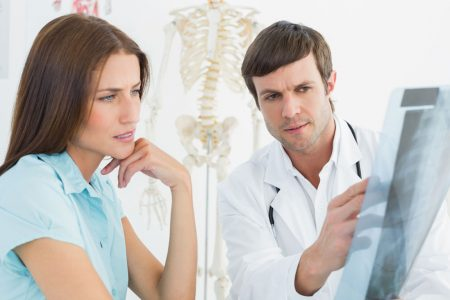chiropractor explaining x-ray to patient